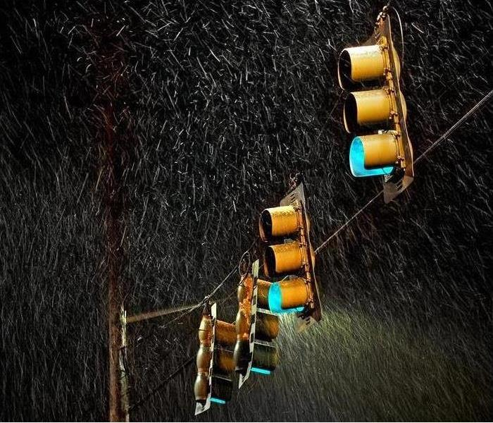 four streetlights swinging in the stormy rain at night