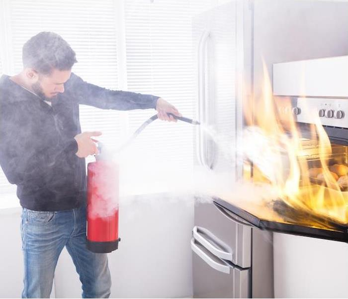 man putting out kitchen fire