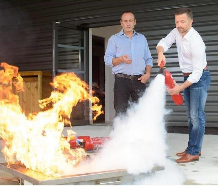 2 men putting out a fire with a fire extinguisher